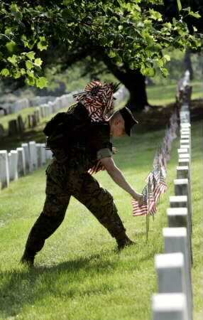 flags are placed in front of graves to honor fallen soldiers who will be remembered on Memorial Day May 31, 2004.