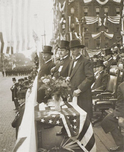 President Theodore Roosevelt, surrounded by flags, reviews a Memorial Day parade in 1907