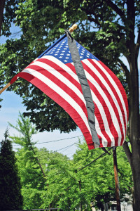 Mourning ribbon flying with an American flag