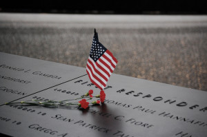 American flag and flowers at the National September 11 Memorial