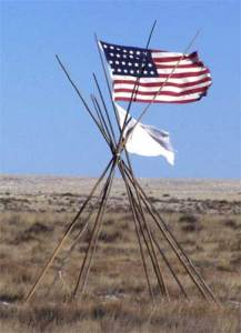 An American flag and  white flag mark the 150th anniversary of Sand Creek. (National Park Service photo)