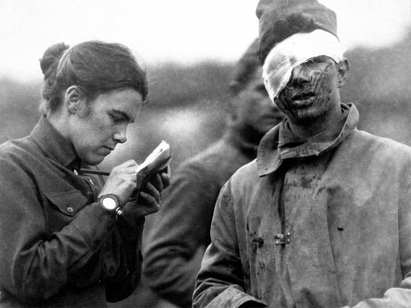 A volunteer writes a letter for a soldier wounded in WWI. (Smithsonian Institution)