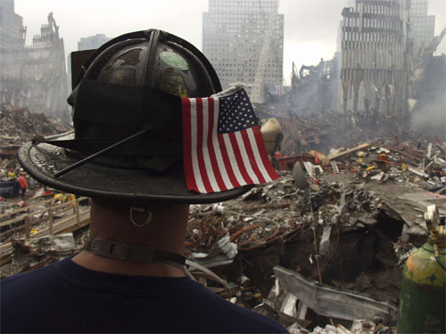A fireman stands amid rubble with a 911 flag on his helmet