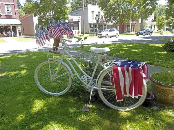 In Angelica, a bike, studded with flags, rests outside a shop. (James Breig photo)