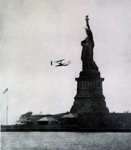 Wright flies around flag on Statue of Liberty island in 1909. (Library of Congress)