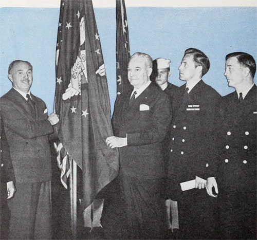 Jack Warner (left) accepts a Victory flag from the Merchant Marines