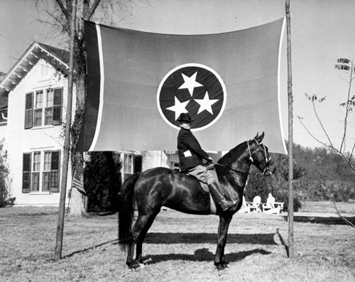 In 1938, a man poses on a horse with the Tennessee state flag as background. (Tennessee State Library and Archives)