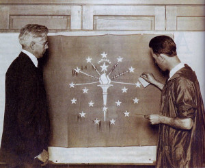 Paul Hadley looks on as an artist applies gold leaf to the state flag. (Mooresville Public Library)