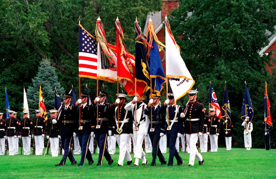 A joint color guard carries the U.S. Flag, Army Service Flag, Marine Corps Flag, Navy Service Flag, Air Force Service Flag, Coast Guard Service Flag.