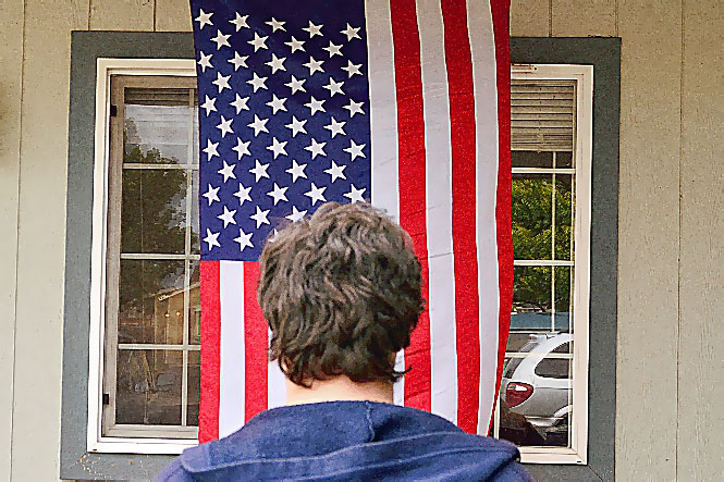 U.S. Flag hanging vertically, with blue field of stars ('canton') at upper left.