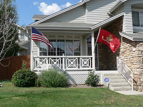Marine Corps flag and American flag flying on the front of a house