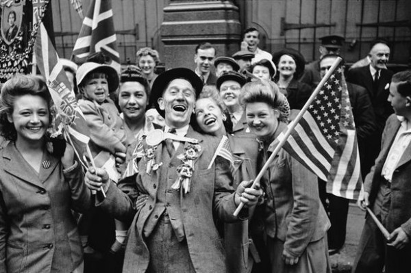 Jubilant British citizens wave flags on V-E Day.