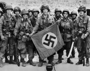 Soldiers display a captured Nazi flag.