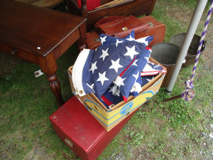 A folded flag lies among yard-sale items. (James Breig photo)