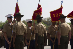Drill instructors take guidons from graduating Marines.