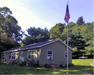 Easy order flag pole outside of a home with an American Flag on it