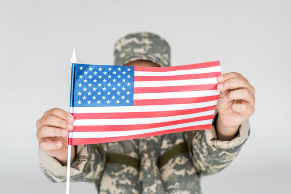 Soldier holding an American Flag obscuring his face