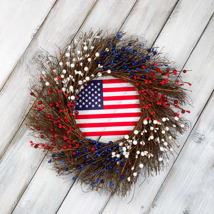 Wreath decorated for Veterans Day with USA flag inside on rustic white wooden boards.