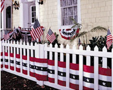 Front of home decorated with American flags, pleated fans and a fence with bunting