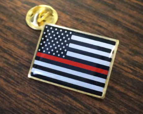 Thin Red Line Lapel Pin on Table