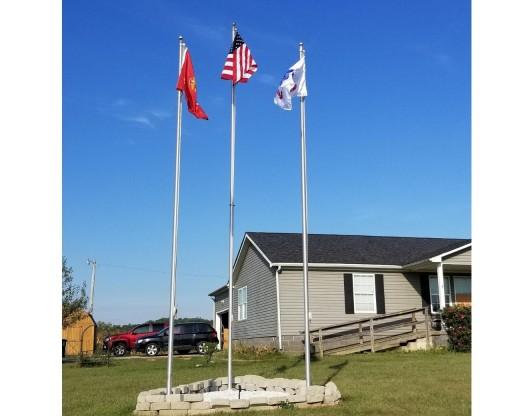 Three aluminum flagpoles in yard