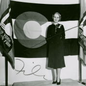 A woman poses before the Colorado flag during the 1939 World's Fair in New York City. (New York Public Library)