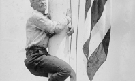 Circa 1920, a man named Edward Flagg shows his love for the American flag by hugging a flagpole. (Library of Congress)